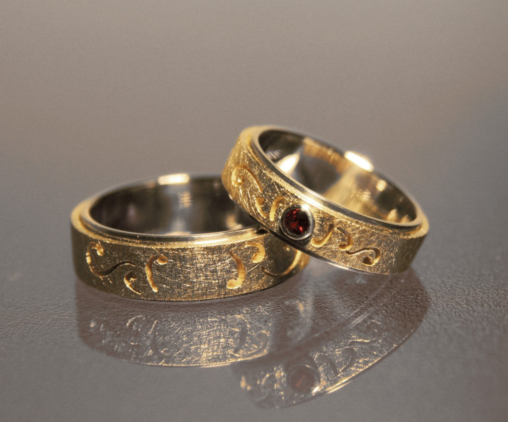 ornate silver and gold wedding bands with ruby