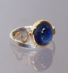 blue sapphie cabochon in a yellow gold setting with a silver band