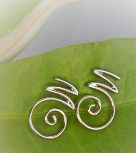 "white gold earrings with the ornamental letter ""M"""